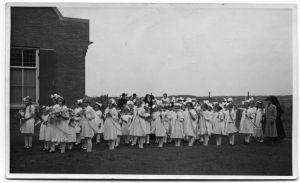 De meisjes van klas twee van de Theresiaschool ter gelegenheid van de opening van de kerk. Rechts (in mantel) juffrouw Stads.